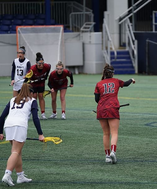 female lacrosse players play on a turf field