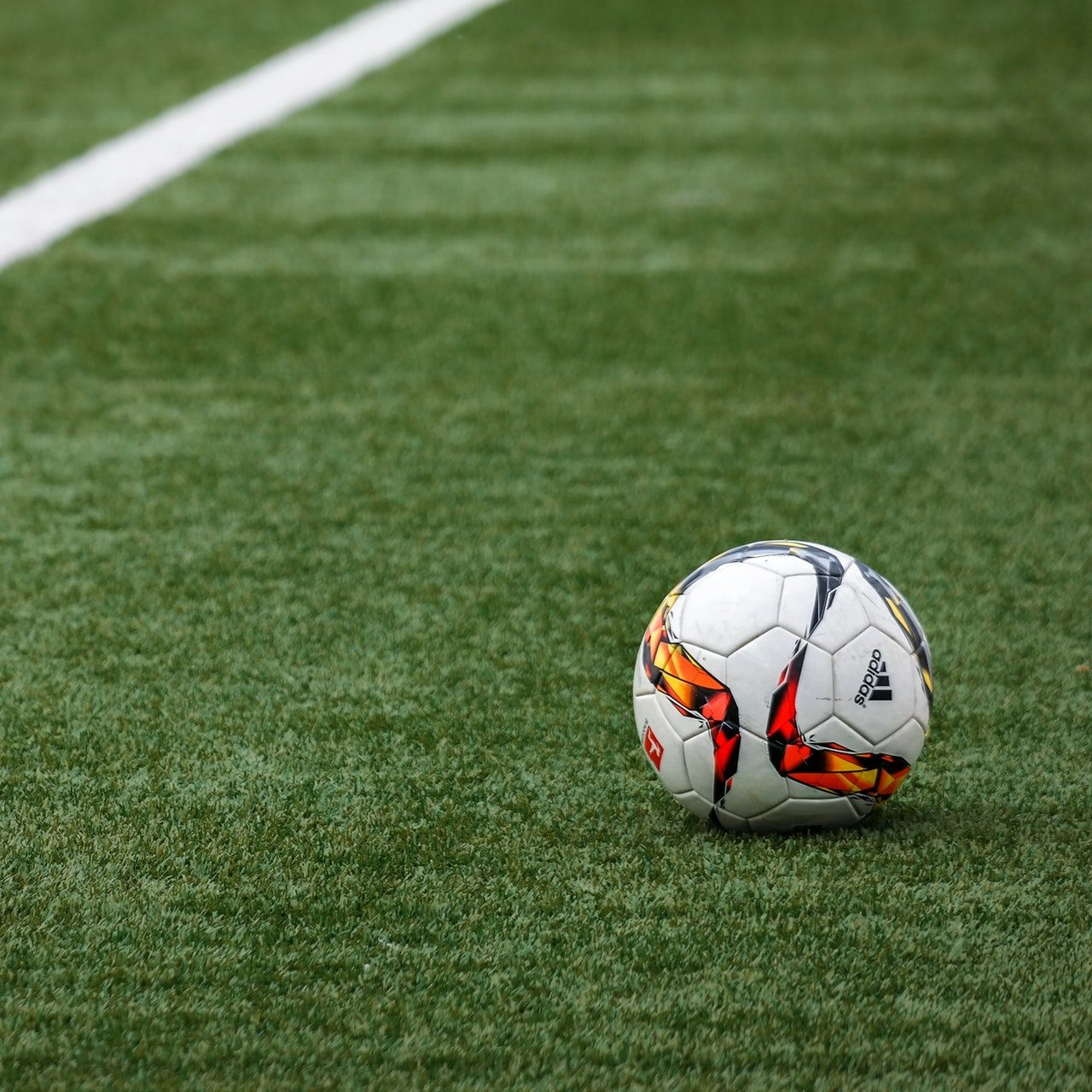 A lone soccer ball sits on a natural turf field
