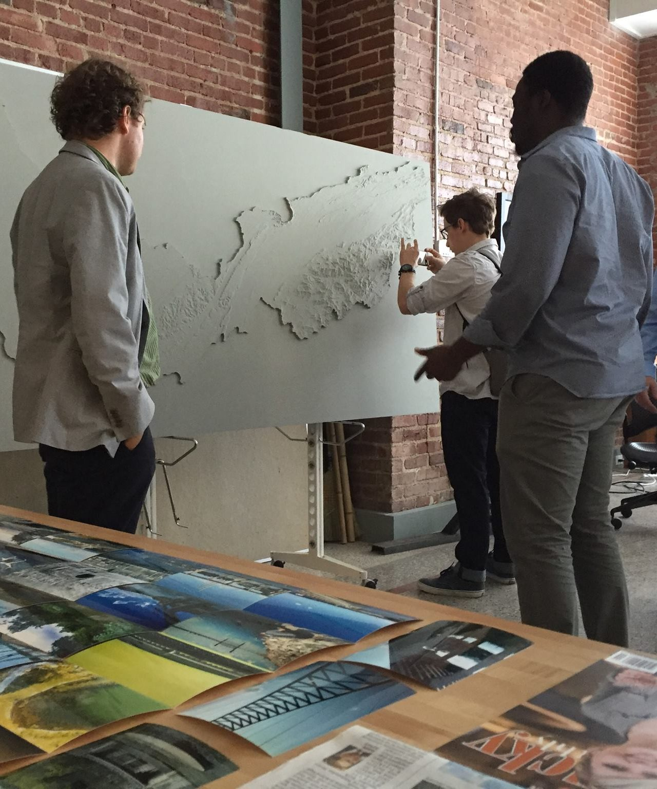 Three students talk over a 3 D map relating to a UT River Studio project