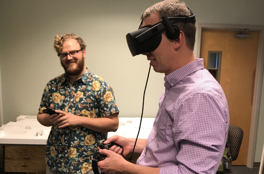 Professor Brad Collett uses virtual reality goggles as a smiling students looks on.