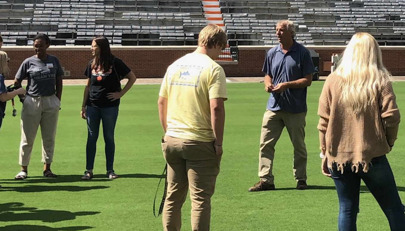 Students and visitors listen as John Sorochan, professor of Plant Sciences, speaks at Neyland Stadium