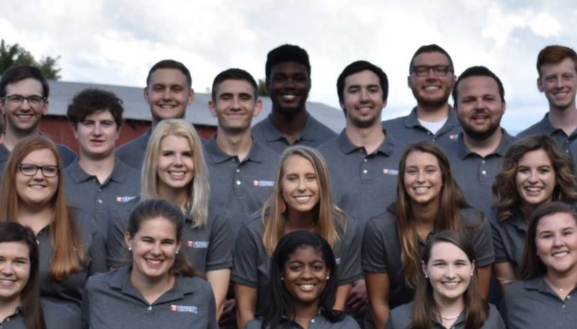 The Herbert Ambassadors, a group of diverse students who lead campus activities, pose in matching grey polos in front of a barn