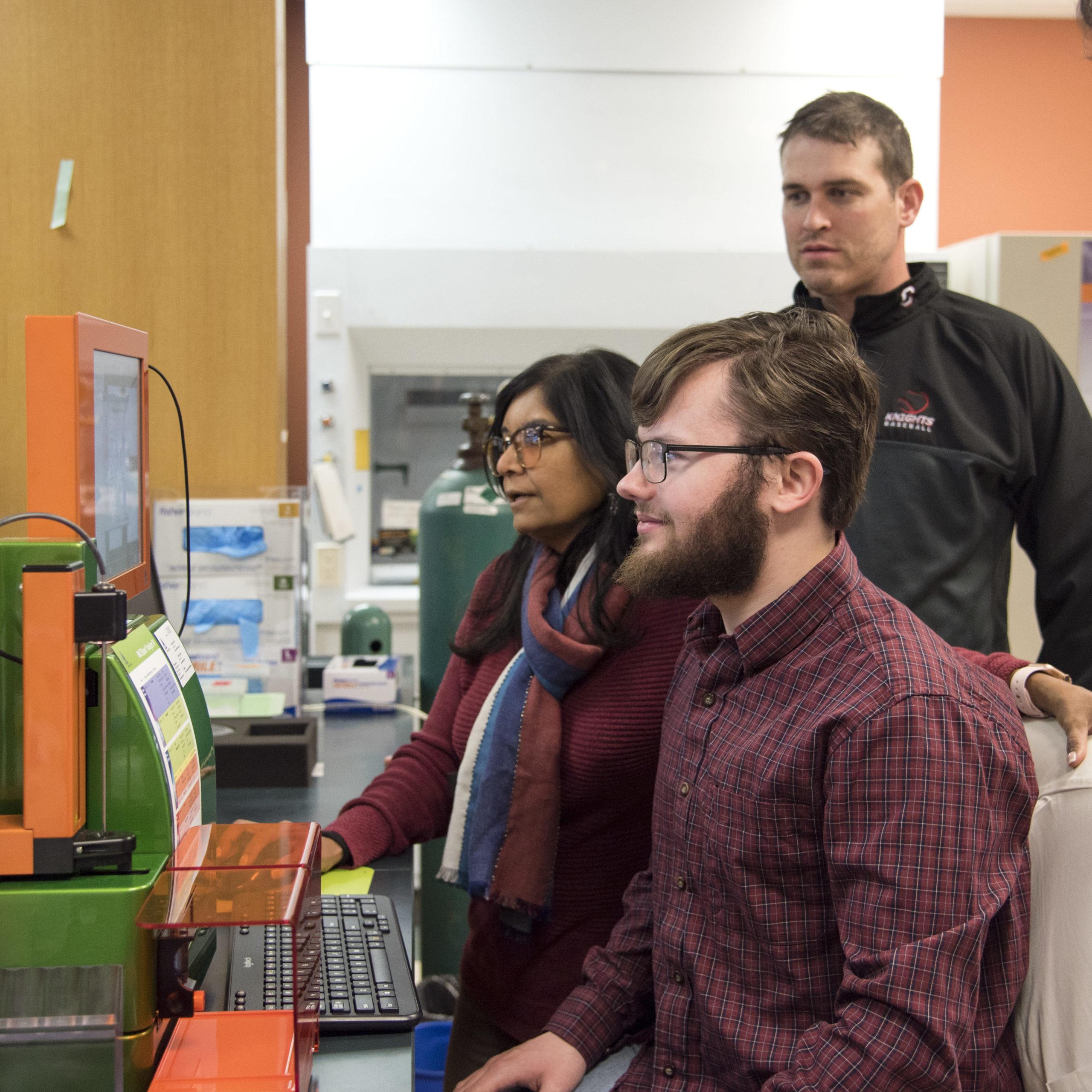Omics hub scientist instruct graduate students on machinery in lab