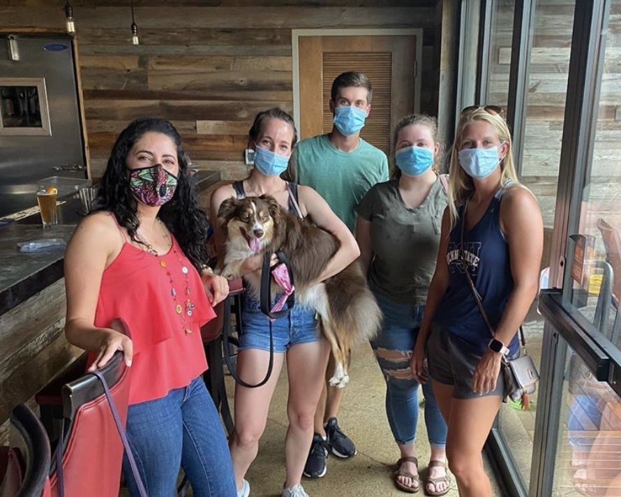 The officers and Tracy Hawk's dog pose with their masks on at a local rooftop bar