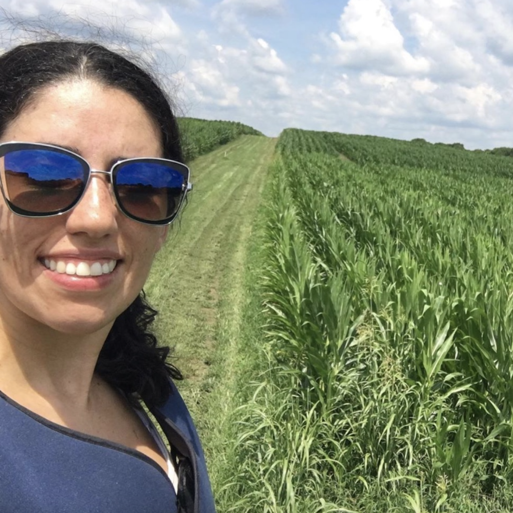 Marcia Pereira Quinby takes a selfie with a forage crop on which she is doing research