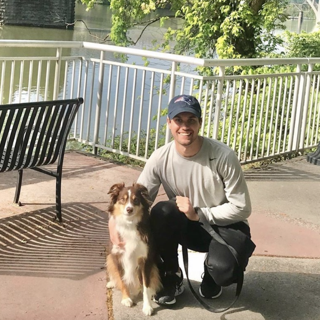 Tyler Carr poses by a city's riverline with his dog
