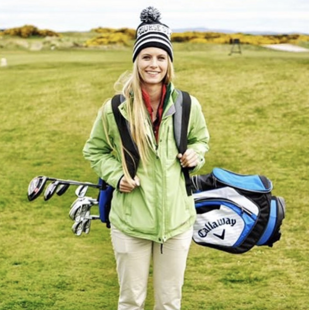 Devon Carroll stands on a golf green with her clubs