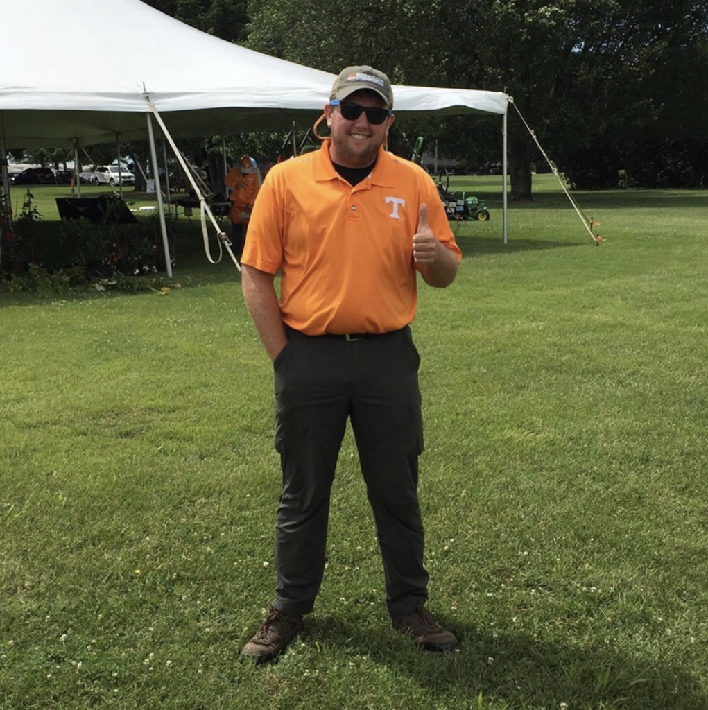Jonathan Kubesch gives a thumbs up in front of a tent at a field day