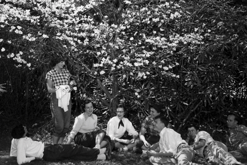 An antique black and white photograph of a group of young people sitting under a dogwood tree.