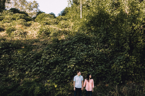 A male and female couple hold hands in front of a bank covered in kudzu vine